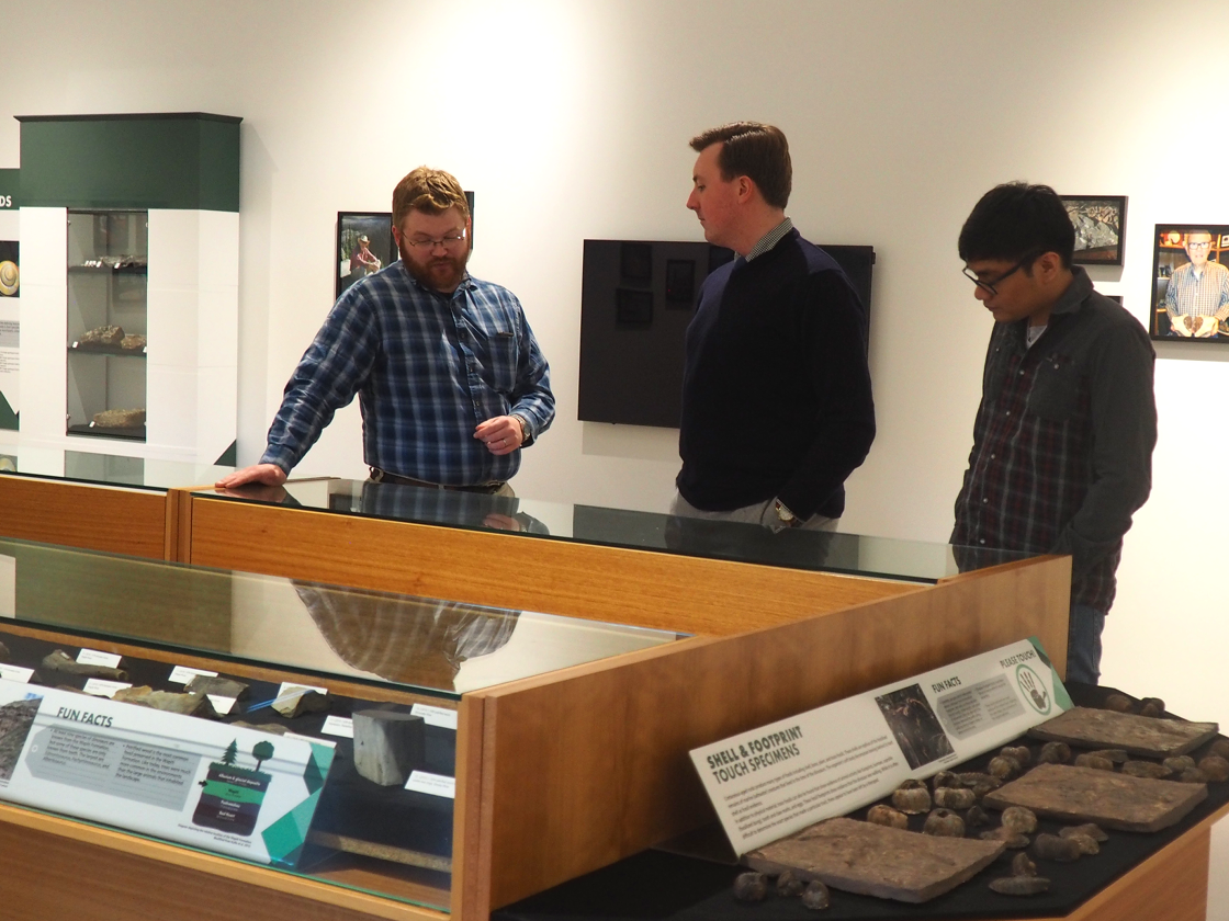 Derek Larson, the museum's assistant curator, explains fossils showcased in the newly opened Roy Bickell Fossil Collection exhibit